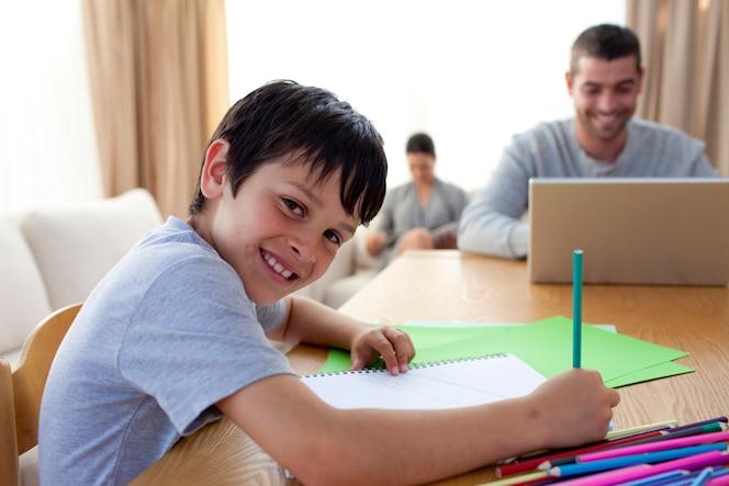 Niño pintando y padre usando una computadora portátil y lectura de la madre