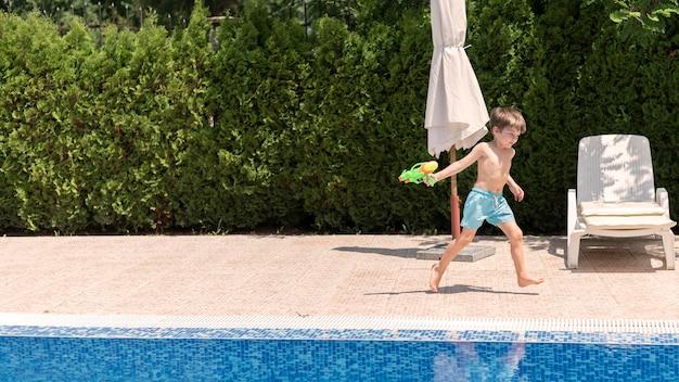 Niño en la piscina jugando con pistola de agua