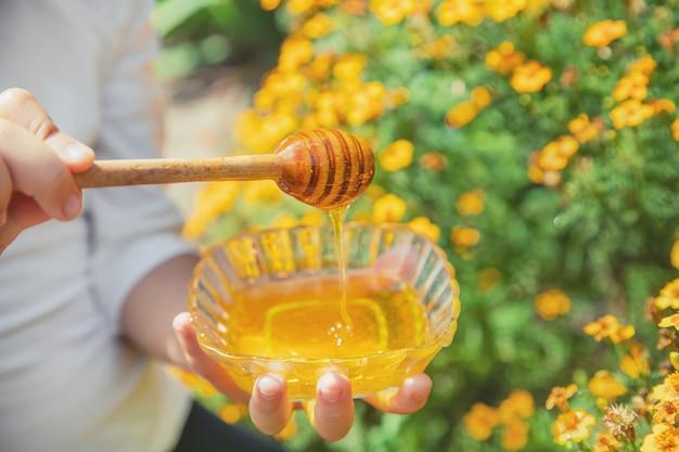 Niño un plato de miel en las manos