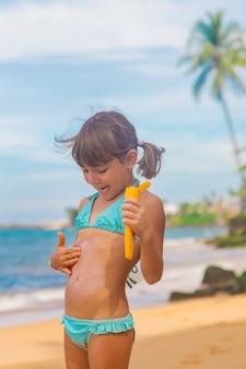 Niño en la playa con protector solar en la espalda. enfoque selectivo. viajar.