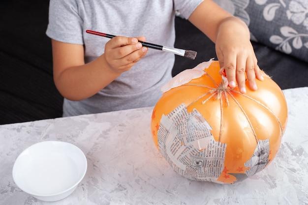 Un niño pone pegamento en un globo para pegar trozos de papel, hace una calabaza con papel maché.