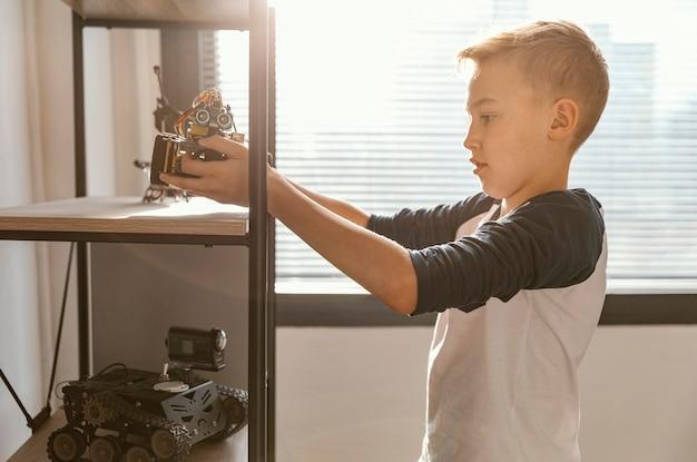 Niño, poniendo, en, estante, robot