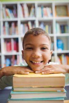 Niño poniendo su cabeza en los libros