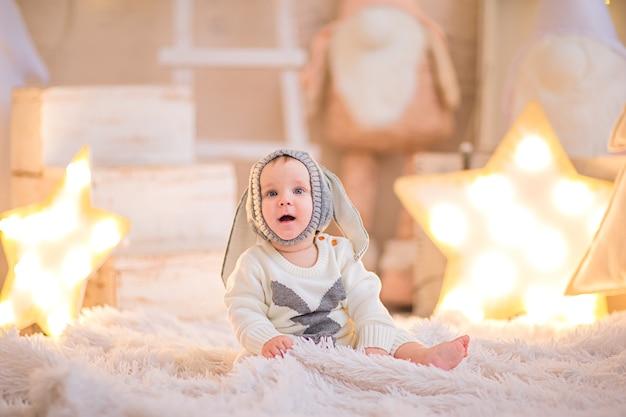 Niño posando en una habitación blanca con fondo de navidad