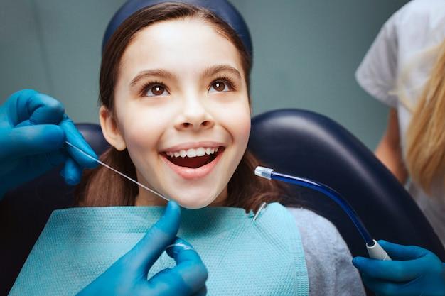 Niño positivo alegre sentarse en la silla dental. manos en guantes de látex para usar hilo dental en los dientes frontales. mujer asisstante se encuentra al lado.