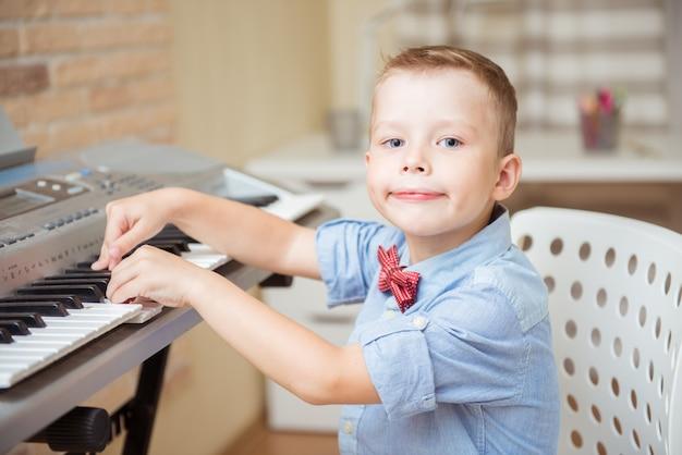 Niño practicando piano eléctrico durante la sesión de música en la academia