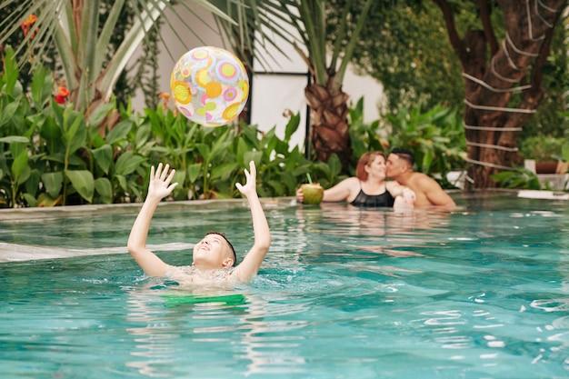 Niño preadolescente emocionado jugando con una pelota inflable en la piscina cuando sus padres se besan en segundo plano.