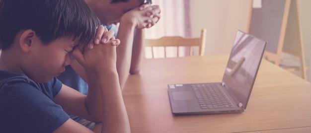 Niño preadolescente orando con padre padre con computadora portátil, familia y niños adoran en línea juntos en casa