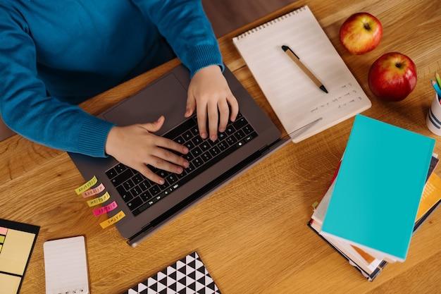 Un niño preadolescente usa una computadora portátil para hacer clases en línea