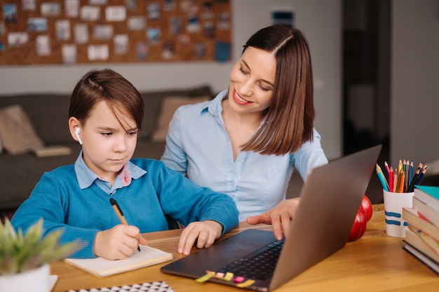 Un niño preadolescente usa una computadora portátil para hacer una videollamada con su maestra junto a su madre