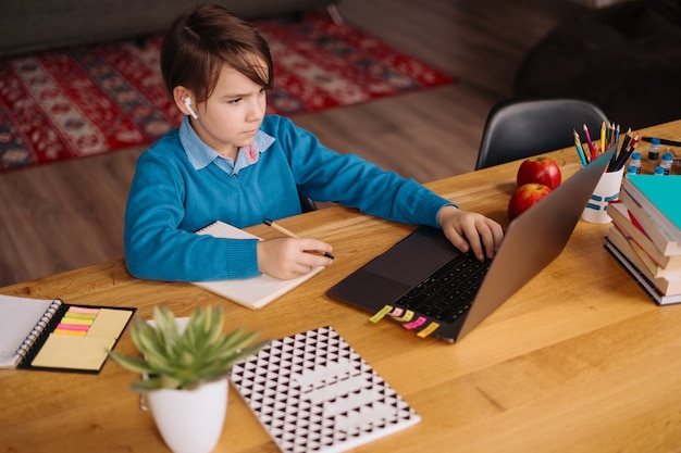 Un niño preadolescente usa una computadora portátil para hacer una videollamada con su maestro, clases en línea, tomar notas