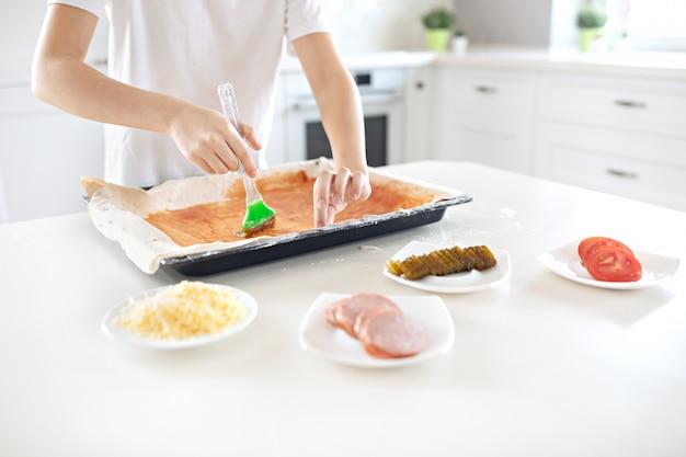 Un niño prepara pizza italiana en la cocina de la casa. el niño lubrica la masa con ketchup. concepto de cocina infantil. estilo de vida, momento franco.
