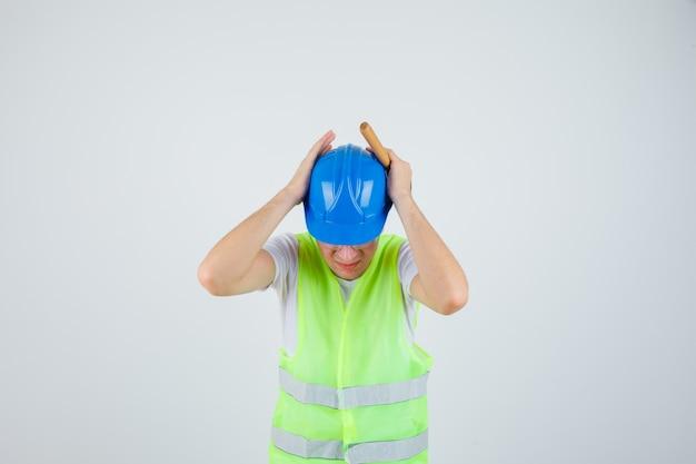Niño presionando las manos en los oídos, sosteniendo un martillo en uniforme de construcción y mirando acosado. vista frontal.