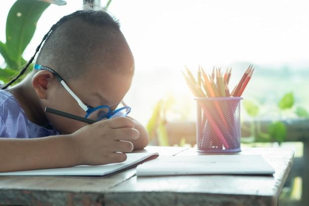 El niño pretende dibujar una imagen divertida, disfrutar dibujar o escribir en un libro en casa.