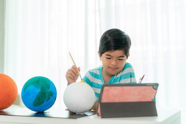 Niño de primaria asiático pintando la luna en clase de ciencias aprendiendo sobre el sistema solar