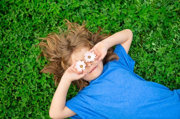 Niño de primavera niño feliz disfrutando en el campo de hierba y soñando niño gracioso con margarita en los ojos
