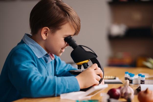 Niño de primer grado estudiando en casa usando microscopio