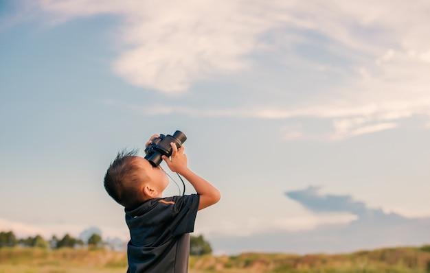 Niño con prismáticos mirando al cielo