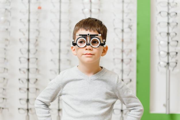 Niño puso marco de prueba en la clínica concepto de óptico médico.
