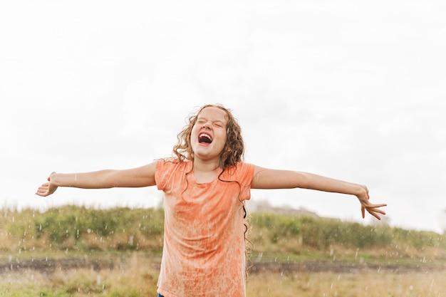 El niño que ríe extiende sus brazos y atrapa las gotas de lluvia.