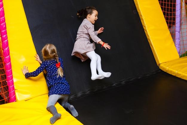 El niño que salta en el trampolín colorido del patio. los niños saltan en la fiesta de cumpleaños inflable castillo de rebote