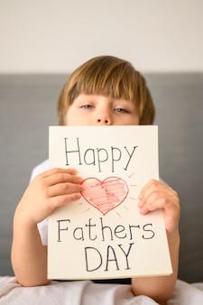 Niño que sostiene la tarjeta de felicitación del día del padre
