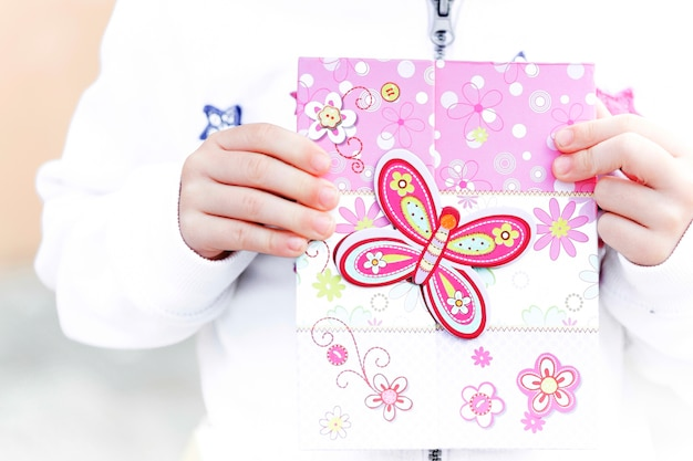 Niño que sostiene la tarjeta de felicitación con diseño de mariposa