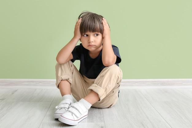 Niño que sufre de dolor de cabeza cerca de la pared de color