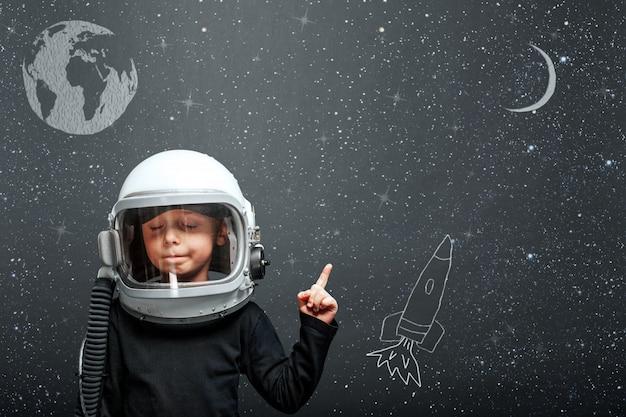 El niño quiere volar un avión usando un casco de avión