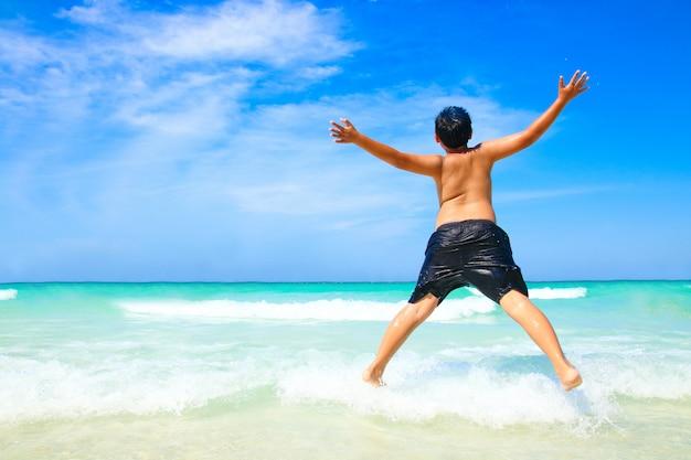 El niño se quitó la camisa y dio un salto. ven a jugar al hermoso mar, playa de arena blanca, agua clara.