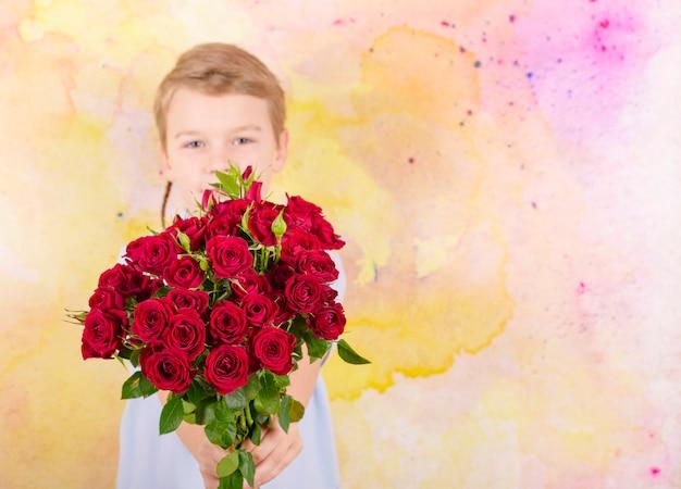 Niño con un ramo de rosas rojas como regalo para el día de la madre o el día de san valentín