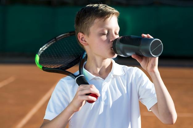 Niño con raqueta en el hombro y agua potable.