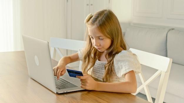 El niño realiza operaciones con una tarjeta de crédito en un portátil.