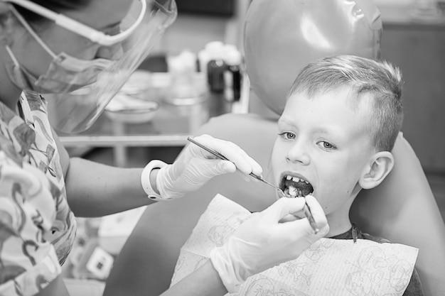 Un niño en la recepción de un dentista en una clínica dental. odontología infantil, odontopediatría. fotografía de estilo retro en blanco y negro. higiene y salud bucal