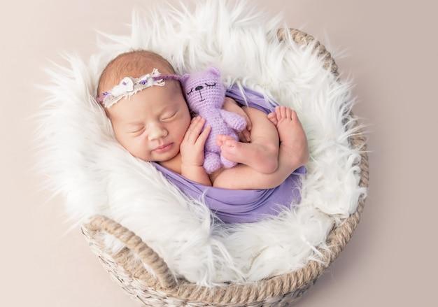 Niño recién nacido en canasta cubierta de lana con juguete