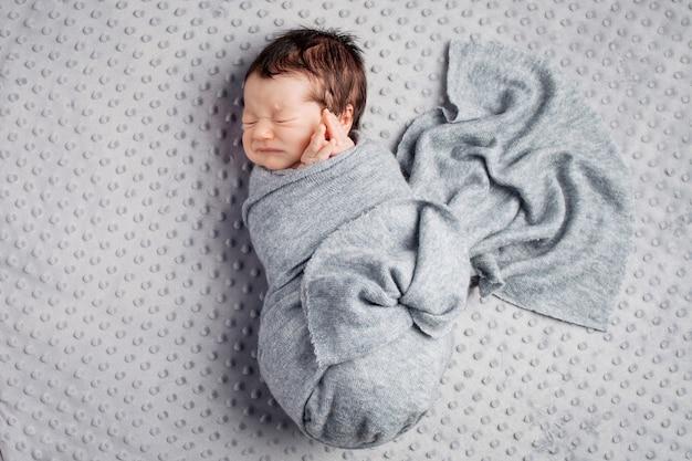 Niño recién nacido en el cocon acostado sobre una manta gris.