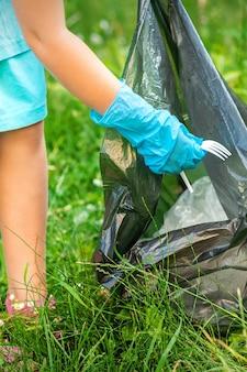 El niño recoge basura plástica de la hierba tirando basura en una bolsa de basura en el parque