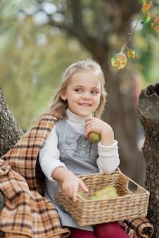 Niño recogiendo manzanas en la granja en otoño