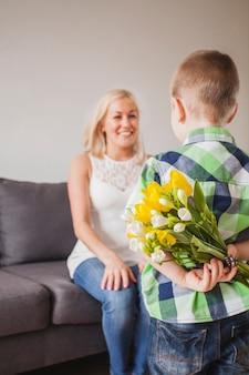 Niño con un regalo sorpresa para su madre