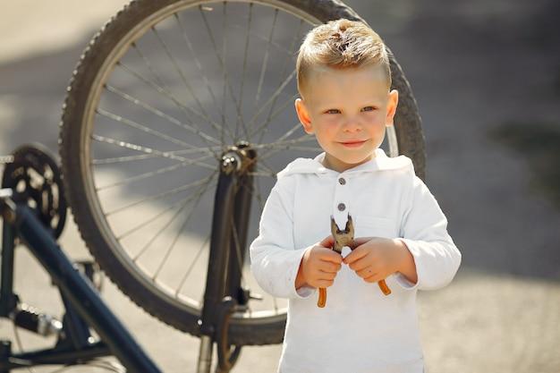 Niño repara su bicicleta en un parque