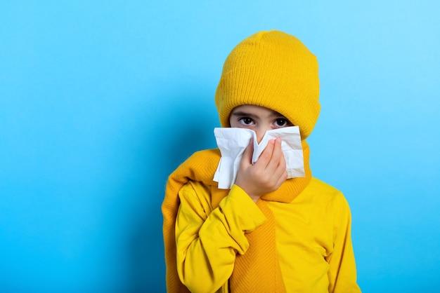El niño se resfrió y se limpia la nariz. fondo cian