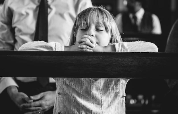 Un niño rezando dentro de la iglesia.