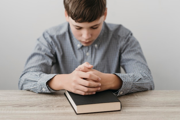Niño rezando con las manos sobre una biblia