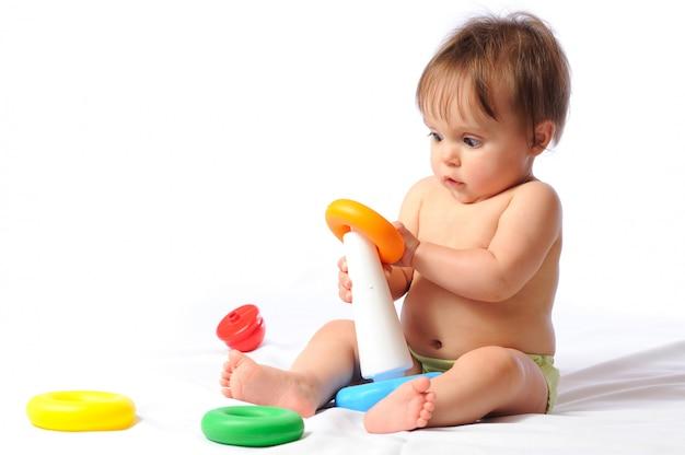 Niño riendo feliz se sienta y juega con el juguete amado.