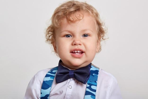Niño rizado guapo con gran hermoso en camisa blanca con pajarita se encuentra en la habitación y tirantes azules, mira a la cámara