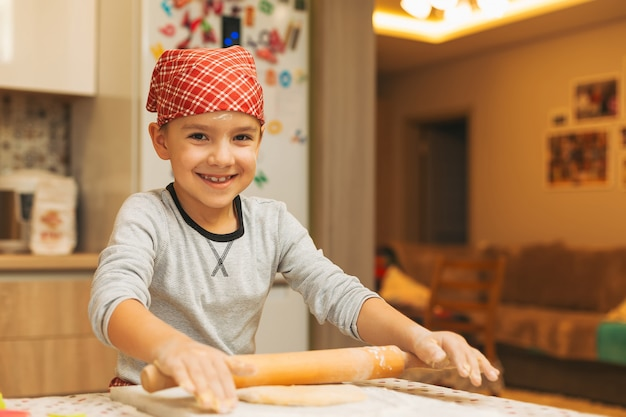 Niño con un rodillo para hornear galletas de navidad