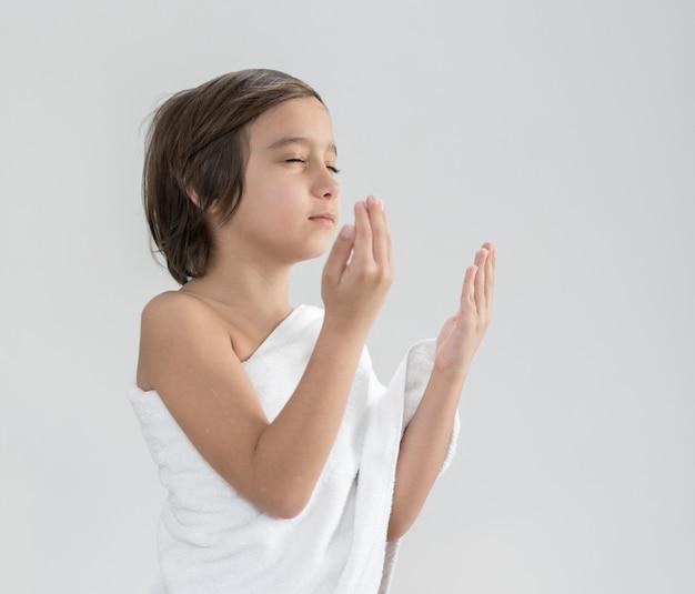 Niño con ropa de peregrinación hajj rezando.