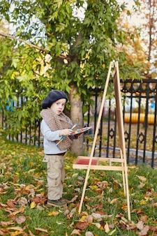 Niño en ropa de primavera otoño retro. pequeño niño sentado sonriendo en la naturaleza, bufanda alrededor de su cuello, clima fresco. emociones brillantes en su rostro.