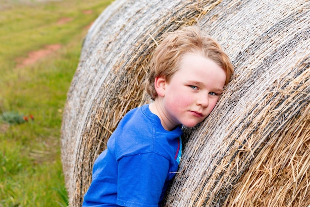Niño rubio apoyado en una larga fila de fardos de heno redondos en días nublados