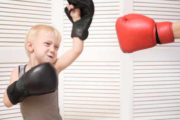 Niño rubio de boxeo con la mano en el guante rojo. las emociones
